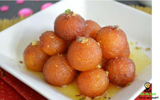 1.Món Gulab jamun Gulab jamun là một trong những món ăn đường phố được nhiều người ưa thích tại Ấn Độ. Nổi bật với hình tròn quả bóng siro màu vàng cánh dán, chỉ cần nhìn thấy là bạn sẽ bị thu hút ngay. Món này được làm từ một loại bột nhão có thành phần chính là sữa. Những viên Gulab jamun được nặn hình tròn đem chiên vàng và ngâm trong siro đường và cho thêm các gia vị khác như nghệ tây, nước hoa hồng, đậu khấu, rau thơm… nhìn rất hấp dẫn. Khi ăn bạn sẽ cảm nhận được vị ngọt ngào từ từ tan chảy trong miệng thơm, ngon tuyệt!